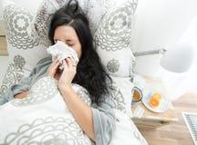 Mujer joven que tiene gripe, soplando su nariz foto de archivo