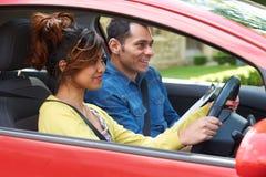 Mujer joven que tiene lección de conducción con el instructor Fotografía de archivo libre de regalías