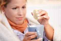 Mujer joven que tiene malo de consumición de la sensación del té de la gripe Foto de archivo
