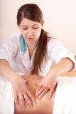 Mujer joven que tiene masaje del estómago. Fotos de archivo libres de regalías