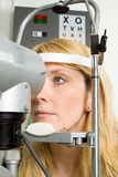 Mujer joven que tiene prueba del ojo Imagenes de archivo