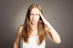 Mujer joven que tiene un dolor de cabeza Imagenes de archivo