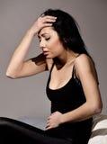 Mujer joven que tiene un dolor de cabeza Fotografía de archivo libre de regalías