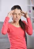 Mujer joven que tiene un dolor de cabeza Fotos de archivo libres de regalías