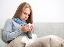 Mujer joven que tiene un frío Imagenes de archivo