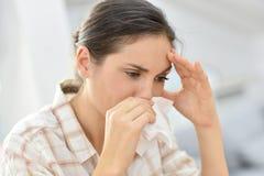 Mujer joven que tiene un frío que sopla su nariz Imágenes de archivo libres de regalías