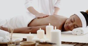 Mujer joven que tiene un masaje en balneario almacen de metraje de vídeo