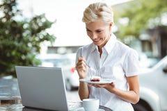 Mujer joven que tiene un pedazo de empanada usando el ordenador portátil Imagen de archivo libre de regalías
