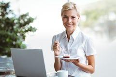 Mujer joven que tiene un pedazo de empanada usando el ordenador portátil Imagenes de archivo