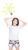 Mujer joven que tiene una idea con la bombilla Imagen de archivo libre de regalías
