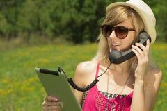 Mujer joven que tiene una llamada de Internet Foto de archivo libre de regalías