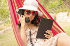 Mujer joven que tiene una llamada de Internet y que miente en hamaca Imagenes de archivo