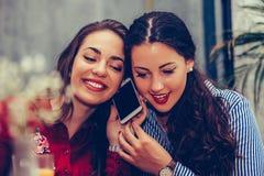 Mujer joven que tiene una llamada de teléfono mientras que su mejor amigo que escucha su conversación imagenes de archivo
