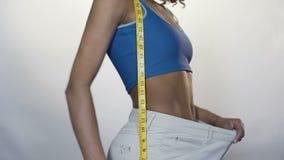 Mujer joven que tira de la cintura de los pantalones adelante, dieta eficaz, pérdida de peso metrajes