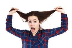Mujer joven que tira de su pelo en el fondo blanco Fotografía de archivo