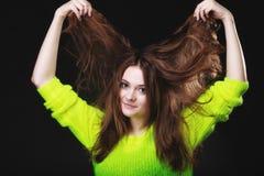 Mujer joven que tira de su pelo largo Imagen de archivo