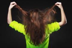 Mujer joven que tira de su pelo largo Fotografía de archivo