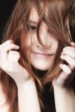 Mujer joven que tira de su pelo largo Fotos de archivo