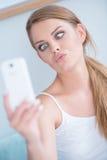 Mujer joven que tira de una cara para el selfie Imagen de archivo libre de regalías