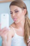 Mujer joven que tira de una cara para el selfie Imágenes de archivo libres de regalías