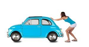 Mujer joven que tira del coche en el backround blanco Foto de archivo libre de regalías