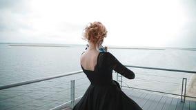 Mujer joven que toca el violín en el muelle en el fondo asombroso de la hermosa vista del río Steadicam s almacen de video