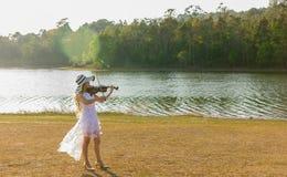 Mujer joven que toca el violín en fondo de la naturaleza Imagen de archivo libre de regalías