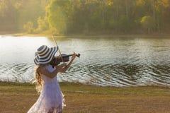 Mujer joven que toca el violín en fondo de la naturaleza Imagenes de archivo