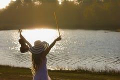 Mujer joven que toca el violín en fondo de la naturaleza Fotografía de archivo libre de regalías
