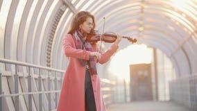 Mujer joven que toca el violín en el paso de arriba almacen de video