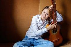 Mujer joven que toca la guitarra Imagenes de archivo