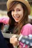 Mujer joven que toca la guitarra Fotografía de archivo libre de regalías