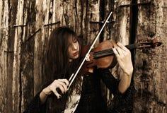 Mujer joven que toca un violín Fotografía de archivo