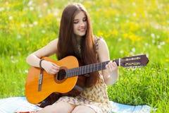 Mujer joven que toca una guitarra Imagenes de archivo