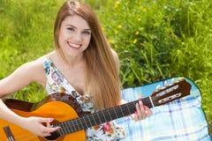 Mujer joven que toca una guitarra Fotografía de archivo