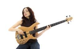 Mujer joven que toca una guitarra baja foto de archivo