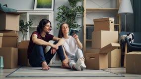 Mujer joven que toma cosas de la caja y que habla con el novio durante la relocalización almacen de metraje de vídeo