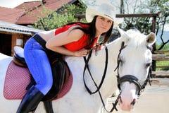 Mujer joven que toma cuidado de su caballo Imagen de archivo libre de regalías