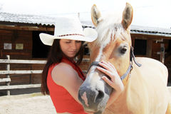 Mujer joven que toma cuidado de su caballo Fotos de archivo libres de regalías