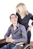 Mujer joven que toma el cuidado del hombre en sillón de ruedas Imagen de archivo libre de regalías
