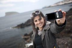 Mujer joven que toma el retrato de uno mismo con el teléfono móvil Fotografía de archivo