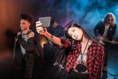 Mujer joven que toma el selfie con la banda de rock-and-roll que realiza concierto Fotos de archivo libres de regalías