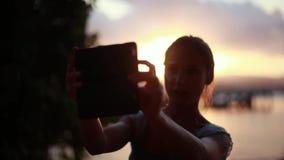 Mujer joven que toma el selfie de la puesta del sol con su teléfono en la playa tropical de Koh Samui 1920x1080 metrajes