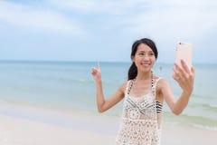 Mujer joven que toma el selfie en la playa de la arena Imágenes de archivo libres de regalías