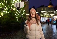 Mujer joven que toma el selfie sobre el árbol de navidad Imagen de archivo