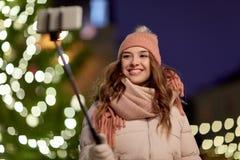 Mujer joven que toma el selfie sobre el árbol de navidad Foto de archivo libre de regalías
