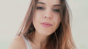 Mujer joven que toma el selfie, usando el teléfono en el dormitorio Sonrisa y hembra blanda por la mañana Cámara lenta metrajes