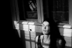 Mujer joven que toma el sol en los rayos del sol en la sombra de los marcos de ventana en el pórtico Foto de archivo