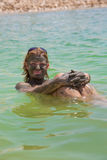 Mujer joven que toma el tratamiento del fango en el mar muerto foto de archivo libre de regalías