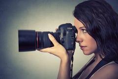 Mujer joven que toma imágenes con la cámara profesional fotos de archivo